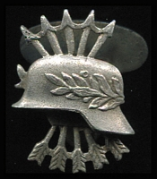 Lot 164 [1 of 2]:Lapel Badge - Spain: for the so-called 'Blue Division' volunteers, a metal badge depicting five Falangists' arrows behind a German helmet showing laurel leaves. The reverse of the badge stamped '8797/A'.